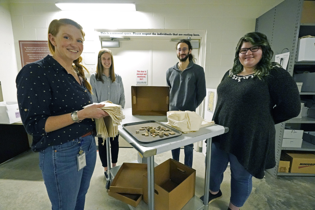 Several hundred ancestral remains and artifacts are being repatriated to the Chickasaw Nation of Oklahoma by the state of Mississippi. Shown here on March 19, 2021 in Jackson, Mississippi, are, from left, Meg Cook, director of the archeology collections for the Mississippi Department of Archives and History; Jessica Walzer, archaeology collections manager; Robert Waren, Native American Graves Protection and Repatriation Act collections manager; and Arianna Kitchens, archaeology collections manager. They are standing by one of the work carts with pottery and lithics that still have not been fully identified. The items will be gathered into hand-constructed muslim for repatriation. (AP Photo/Rogelio V. Solis)