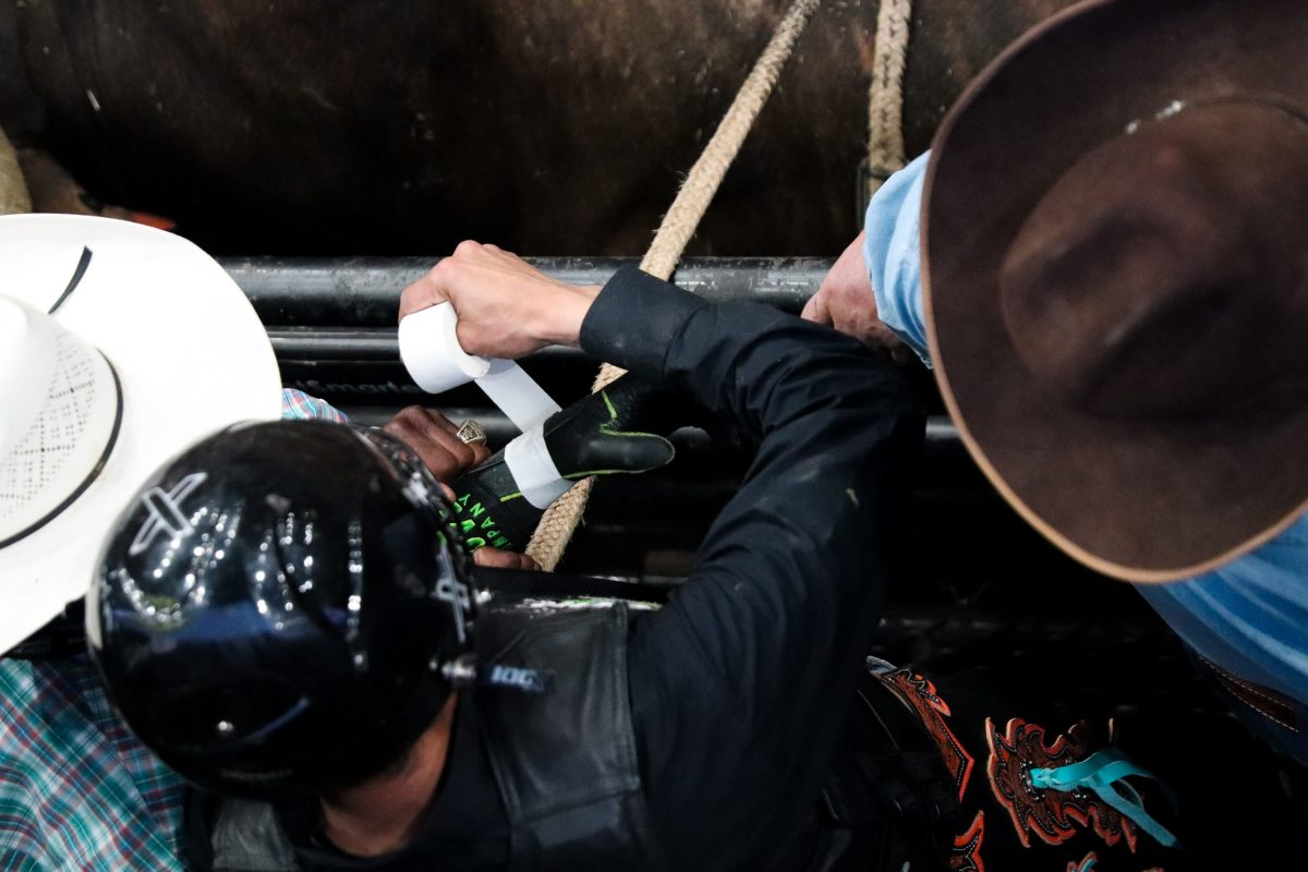 Jesus wraps tape around his glove before his ride in round 2. (Photo by Marlee Smith/Cronkite News)