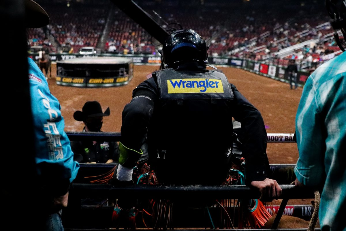 Cody Jesus stretches in the chutes as the opening rider for the Built Ford Tough Invitational in his home state of Arizona. (Photo by Marlee Smith/Cronkite News)