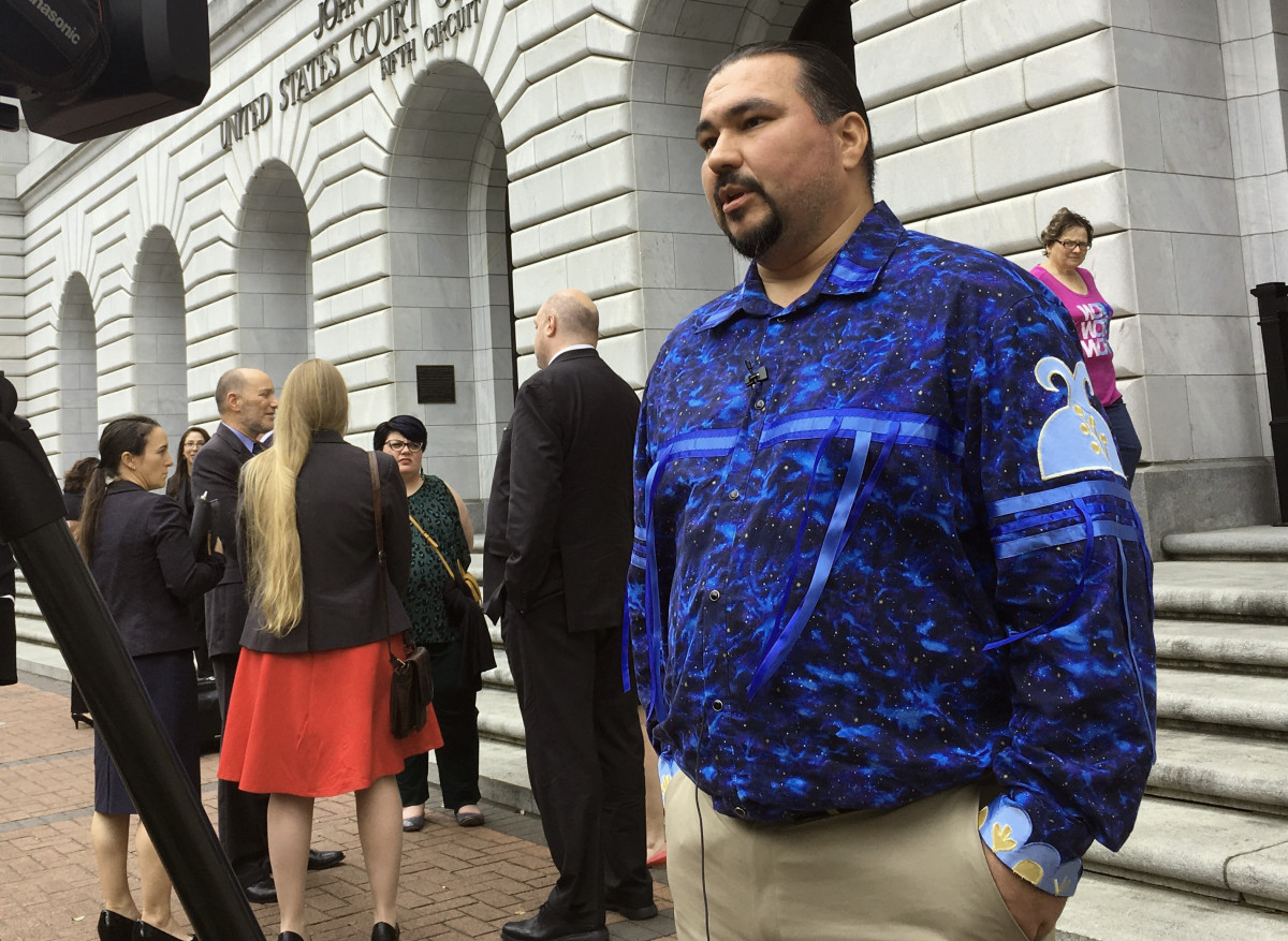 Tehassi Hill, tribal chairman of the Oneida Nation, stands outside a federal appeals court Wednesday, March 13, 2019 in New Orleans, following arguments on the constitutionality of a law giving Native American families preference in adoption of Native American children. A Texas-based federal judge ruled the 1978 law unconstitutional last year. Hill is among leaders of various Native American tribes hoping the 5th U.S. Circuit Court of Appeals will reverse the ruling and uphold the law. (AP Photo/Kevin McGill)