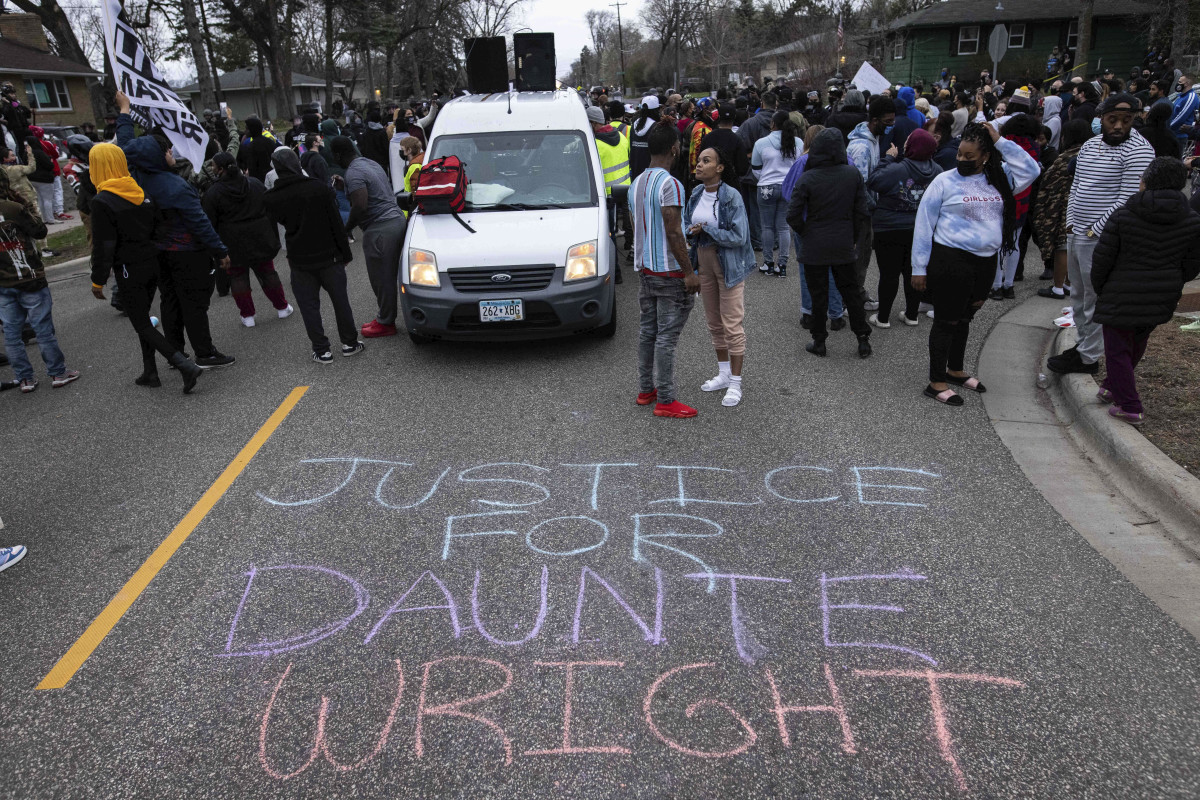 People gather in protest, Sunday, April 11, 2021, in Brooklyn Center, Minn. The family of Daunte Wright, 20, told a crowd that he was shot by police Sunday before getting back into his car and driving away, then crashing the vehicle several blocks away. The family said Wright was later pronounced dead. (AP Photo/Christian Monterrosa)