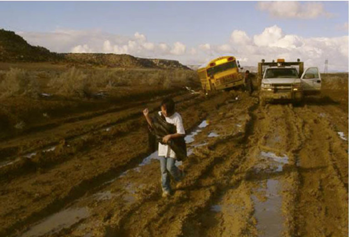 Roads are another problem on tribal lands. In this file photo, a Navajo student walks away from a school bus that was stuck in the mud on an unpaved road. (Photo courtesy San Juan County, Utah, Roads Department)