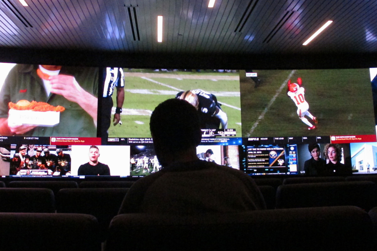 In this Nov. 20, 2018 photo, a customer watches video screens at a sportsbook in Atlantic City, N.J. On Thursday, March 11, 2021, BetMGM and Buffalo Wild Wings launched a program where special sports betting products are offered to customers at one of the chain's restaurants in New Jersey, Colorado, Indiana, Iowa, Tennessee and West Virginia. (AP Photo/Wayne Parry)