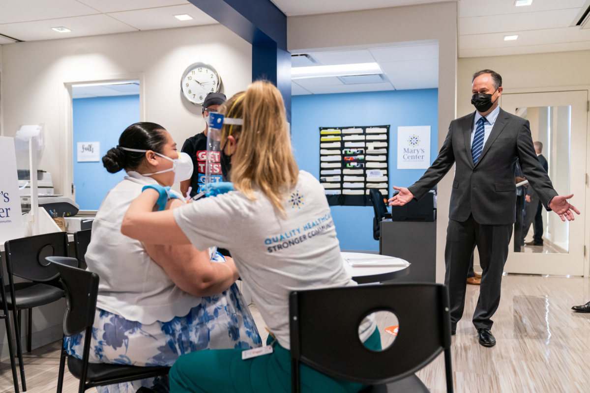 Second Gentleman Douglas Emhoff looks on as Jessica Palacios receives a COVID-19 vaccine from nurse Eva Sweeny Tuesday, March 30, 2021, at Mary's Center in Silver Spring, Maryland. (Official White House Photo by Cameron Smith)