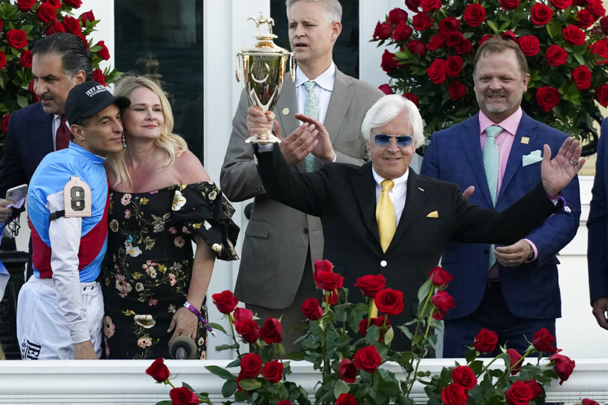 Jockey John Velazquez, left, watches as trainer Bob Baffert holds up the winner's trophy after they victory with Medina Spirit in the 147th running of the Kentucky Derby at Churchill Downs, Saturday, May 1, 2021, in Louisville, Ky. (AP Photo/Jeff Roberson