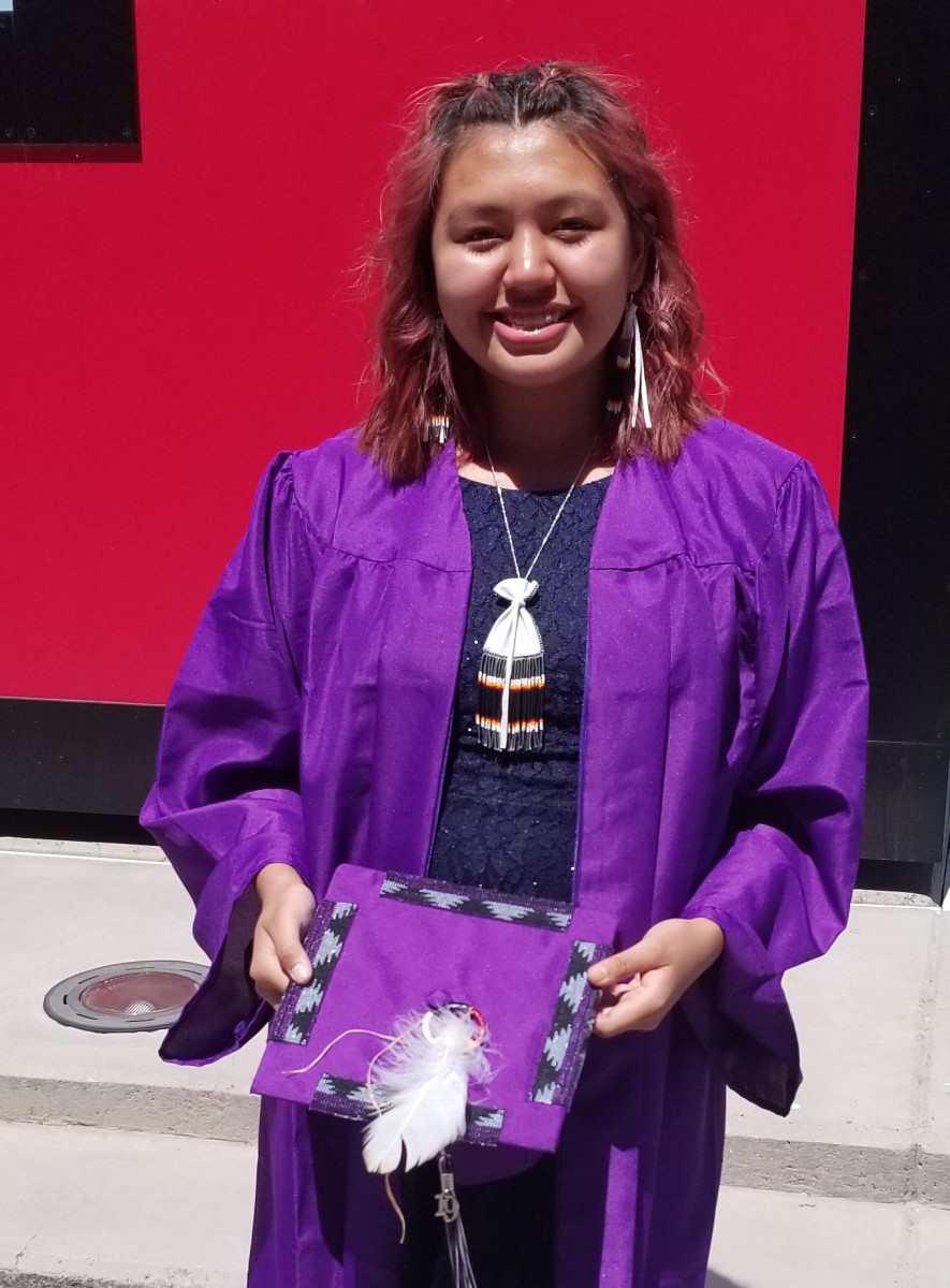 Larissa Waln holds the eagle plume and beaded cap that she wanted to wear during her graduation in 2019. (Photo courtesy of Bryan Waln)