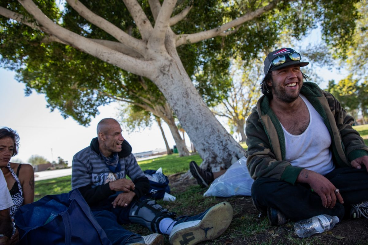 """Terry Wilson, 29, right, laughs as he and his friends talk about their experiences using drugs in Yuma, Ariz., on March 6, 2021. The proximity to the border with Mexico makes Yuma an easy target for street traffickers. """"Towns like this, where everyone knows everyone – people think that sounds nice, but here it just means every loss is personal,"""" Wilson says. (Photo by Alberto Mariani/Cronkite News)"""
