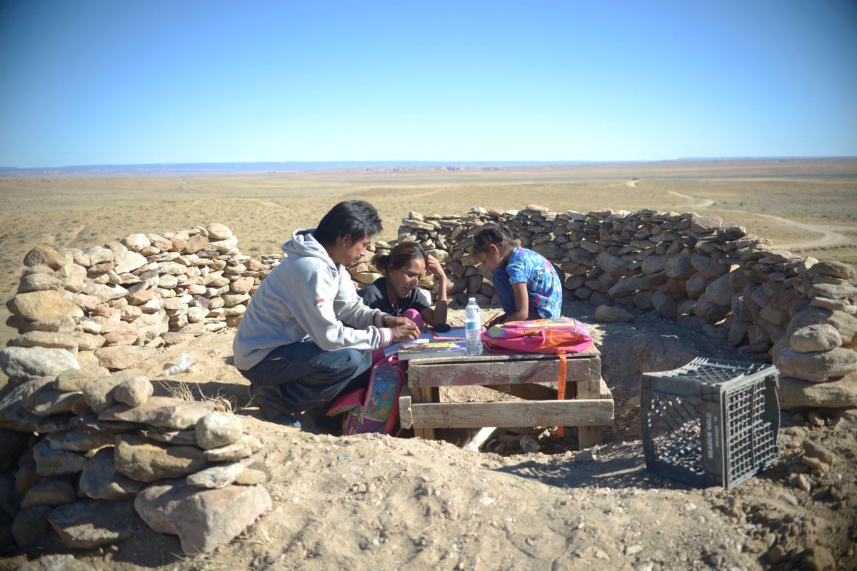 Pictured: Makeshift Classroom, Fish Point, Arizona, Navajo Nation, October 19, 2020. Milton T. Carroll and Wylean Burbank help their daughter Kyla with her schoolwork in a makeshift outdoor classroom. Kyla is a first-grader at Cottonwood Day School, a Bureau of Indian Education school. Carroll constructed the makeshift classroom on top of a hill near their home so that, hopefully, the family could receive cell phone reception and Wi-Fi service. Having neither in their home, their daughter was unable to do her homework. Carroll later modified the classroom by expanding the walls and adding a woodstove for warmth. As ofFebruary2021, the Navajo Tribal Utility Authority was trying to install Wi-Fi service in their home.