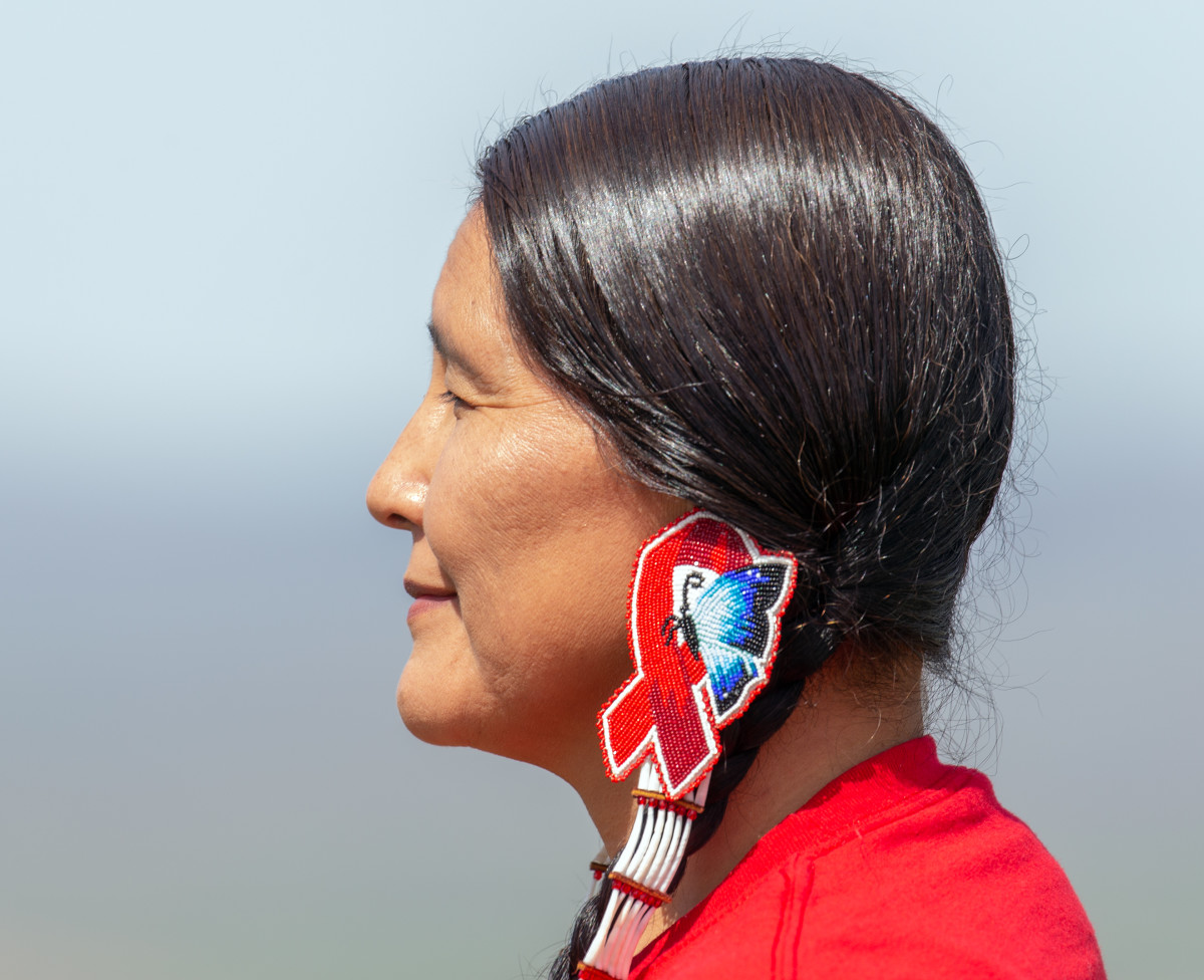 Merle Kirk, who lives on the Umatilla Indian Reservation, wears earrings she beaded in honor of her sister, Mavis Kirk-Greeley, and cousin, Lisa Pearl Briseno. (Photo by Kathy Aney, Underscore)
