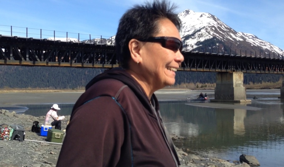 """Becky Etukeok Johnson, who is Tlingit, Filipino, and Inupiaq, laughed after saying, """"I like to fish with my cousins. They're my kind of crazy,"""" while standing on the banks of the Twentymile River outside of Anchorage, Alaska, where dipnetting for eulachon fish was underway on May 18, 2021. (Photo by Joaqlin Estus, Indian Country Today)"""