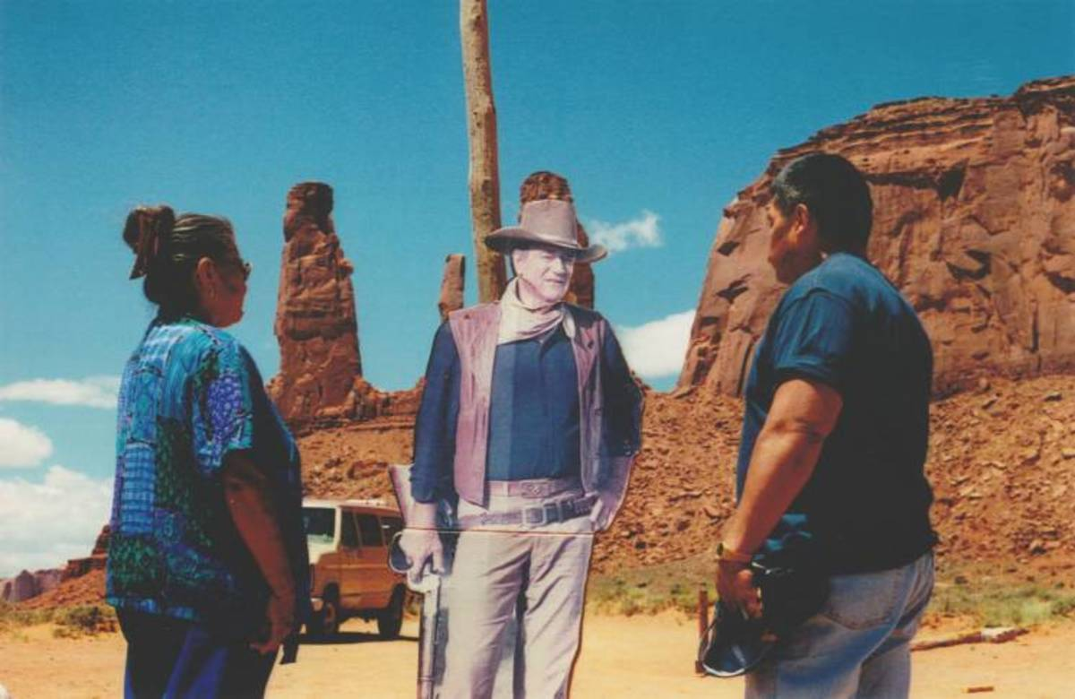 Elsie Mae Begay and her brother John Wayne Cly look at a cardboard cut-out of his namesake. (Courtesy Jeff Spitz)