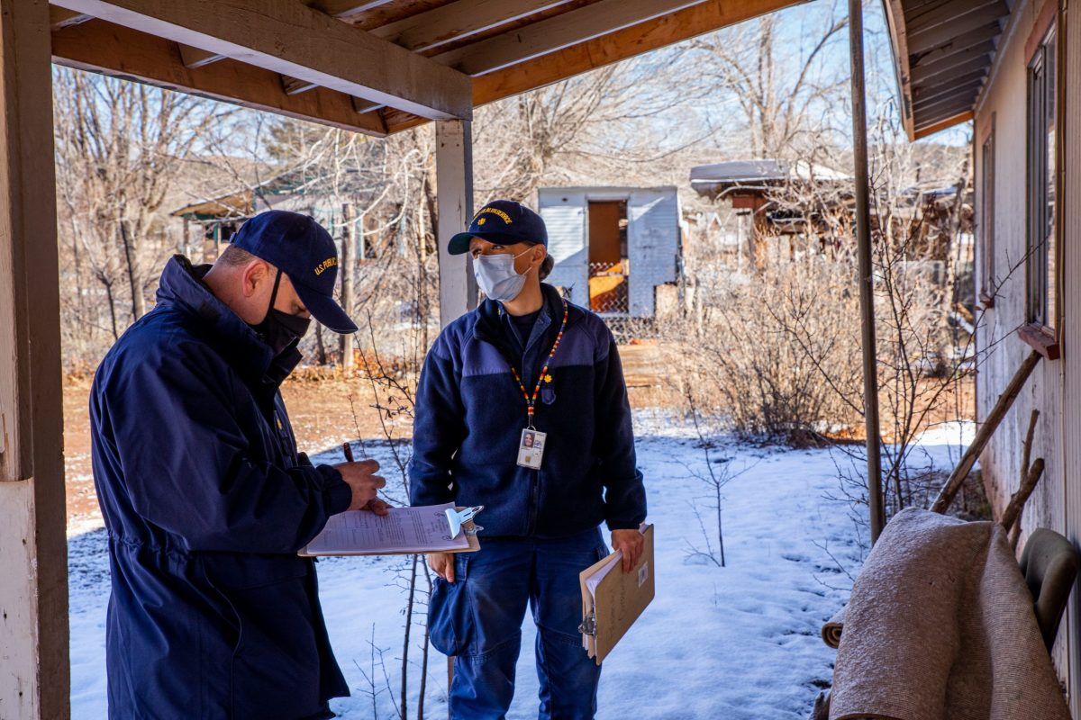 Justin Tafoya, left, and Kristen Parker visit the home of a White Mountain Apache who's scheduled for a COVID-19 vaccination in Whiteriver, Ariz. on Feb. 17, 2021. Parker is a pharmacist and outreach director at Whiteriver Indian Hospital; Tafoya, a registered nurse, serves as a public information officer. (Photo by Alberto Mariani/Cronkite News)