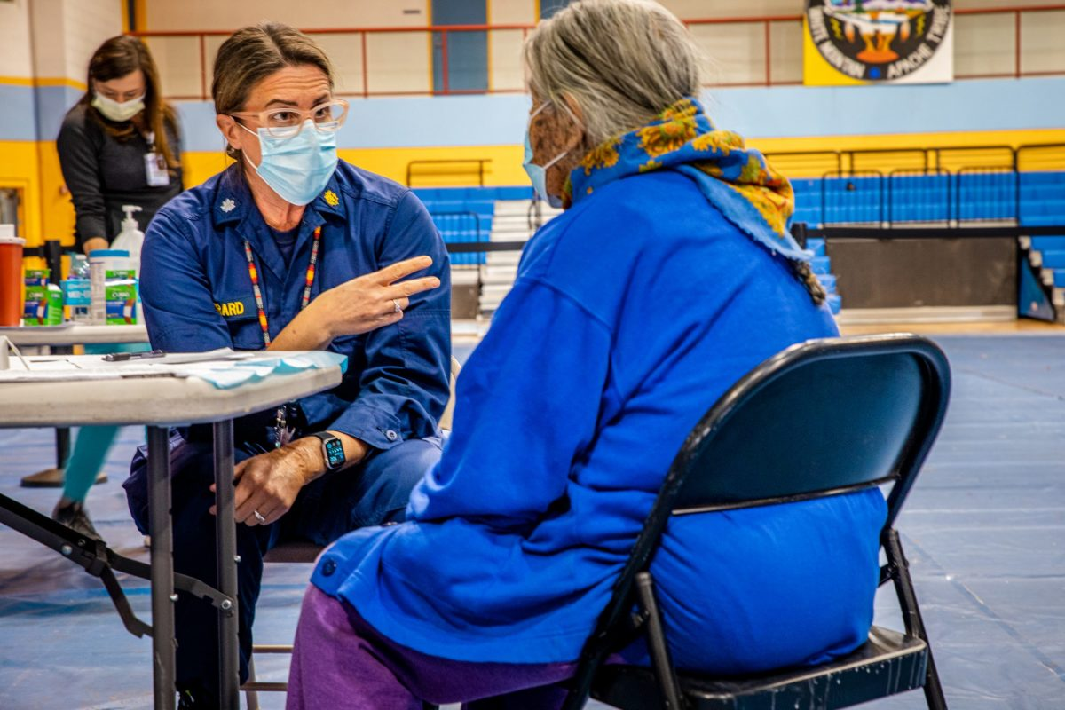 A medical assistant explains the vaccination procedure to a member of the White Mountain Apache Tribe at a vaccination event inside Whiteriver's gymnasium on Feb. 17, 2021. (Photo by Alberto Mariani/Cronkite News)