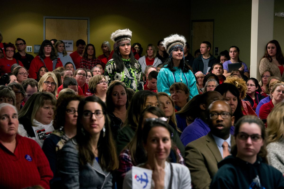Wearing her Yup'ik headdress, Nyché Andrew, right, waits to testify at the Anchorage School Board meeting on Nov. 5, 2018. Her sister Farrell Stoudt joined her for support. Nyché, then a sophomore at Service High School, testified in favor of a new regulation to allow students to wear traditional regalia during graduation ceremonies. (Marc Lester / ADN)