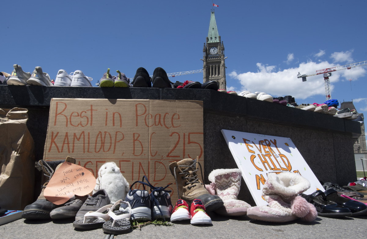 Shoes sit on the Eternal flame in recognition of discovery of children's remains at the site of a former residential school in Kamloops, British Columbia, on parliament hill in Ottawa, Ontario, on Monday May 31, 2021. (Adrian Wyld/The Canadian Press via AP)