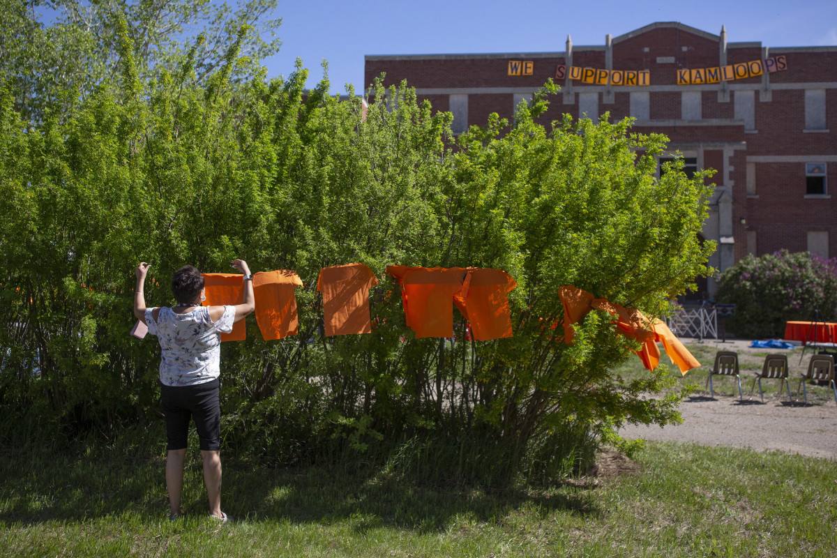 Volunteers put up orange shirts before a press conference and prayer vigil at the former Muscowequan Indian Residential School, one of the last residential schools to close its doors in Canada in 1997 and the last fully intact residential school still standing in Saskatchewan at Muskowekwan First Nation, Saskatchewan, on Tuesday, June 1, 2021. The vigil was in response to the remains of 215 children recently found at the Kamloops Indian Residential School. (Kayle Neis/The Canadian Press via AP)