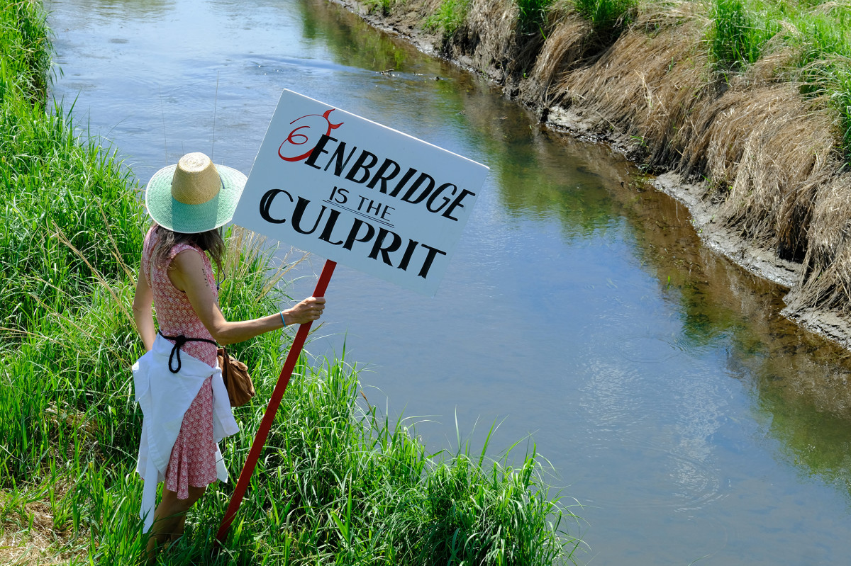 """Mary Rosenberg, who was born and raised in Park Rapids joins water protectors along Mississippi River, one of Line 3 crossings in Solway, MN. """"My dad was a fishing guide in this area; I had to come down and touch this water in his memory. (Photo by Mary Annette Pember) June 7"""