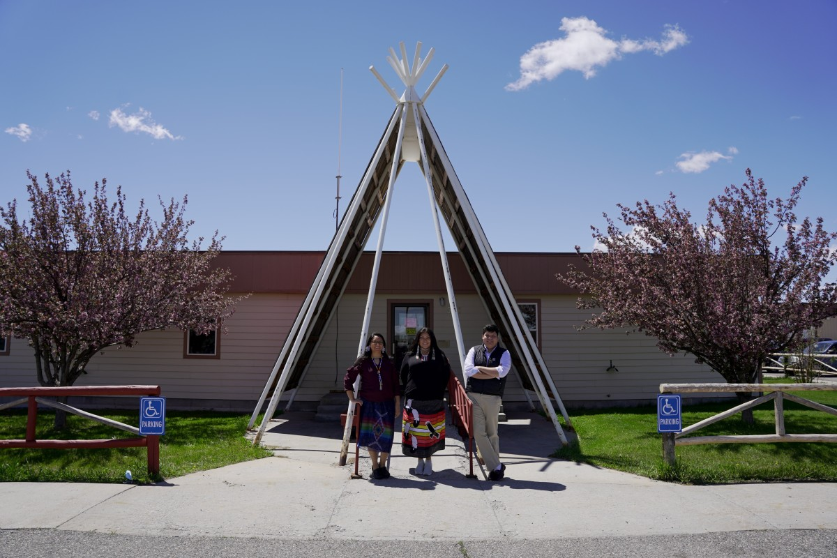 The Northern Arapaho Tribal Housing Department opened the first government office in Wyoming to open a special program to hand out pandemic assistance to renters; it is now a model for the statewide program. Here, program director Lynette Grey Bull, center, stands at the tepee-like entrance with intake specialists Tamara Duran, left, and Stephin Littleshield, right, in May 2021. (Photo by Christian Collins for Indian Country Today)