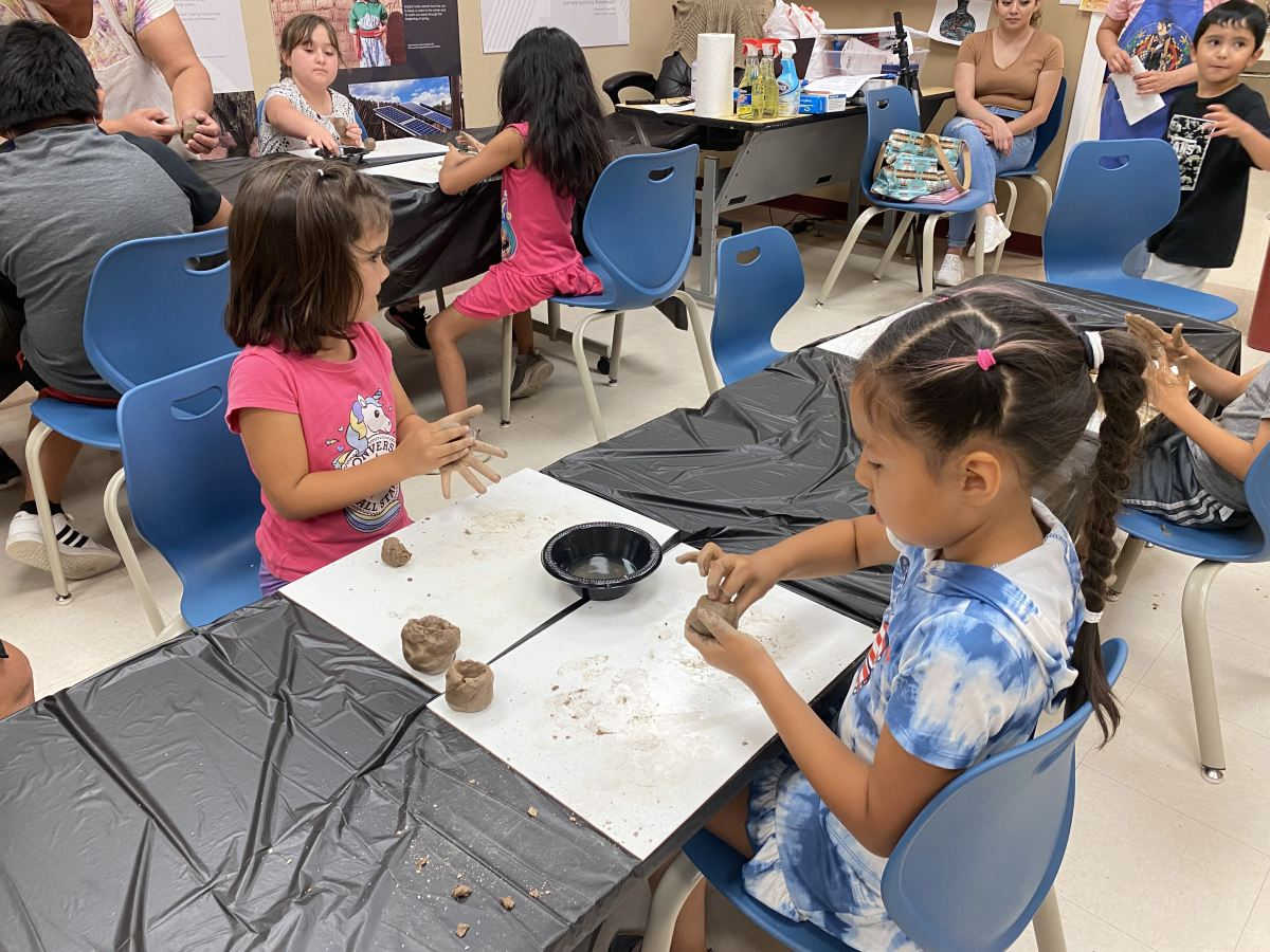 """Campers use water to mold pieces of clay into small pots at the """"traditional teachings"""" summer camp in Albuquerque, NM. (Photo by Aliyah Chavez, ICT)"""