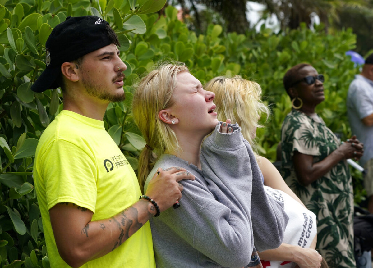 Ariana Hevia, of New Orelans, La., center, stands with Sean Wilt, left, near the 12-story beachfront condo building which partially collapsed, Friday, June 25, 2021, in the Surfside area of Miami. Hevia' s mother Cassandra Statton lives in the building. Search and rescue teams continue to work at the site hoping to detect any sounds coming from survivors. (AP Photo/Lynne Sladky)
