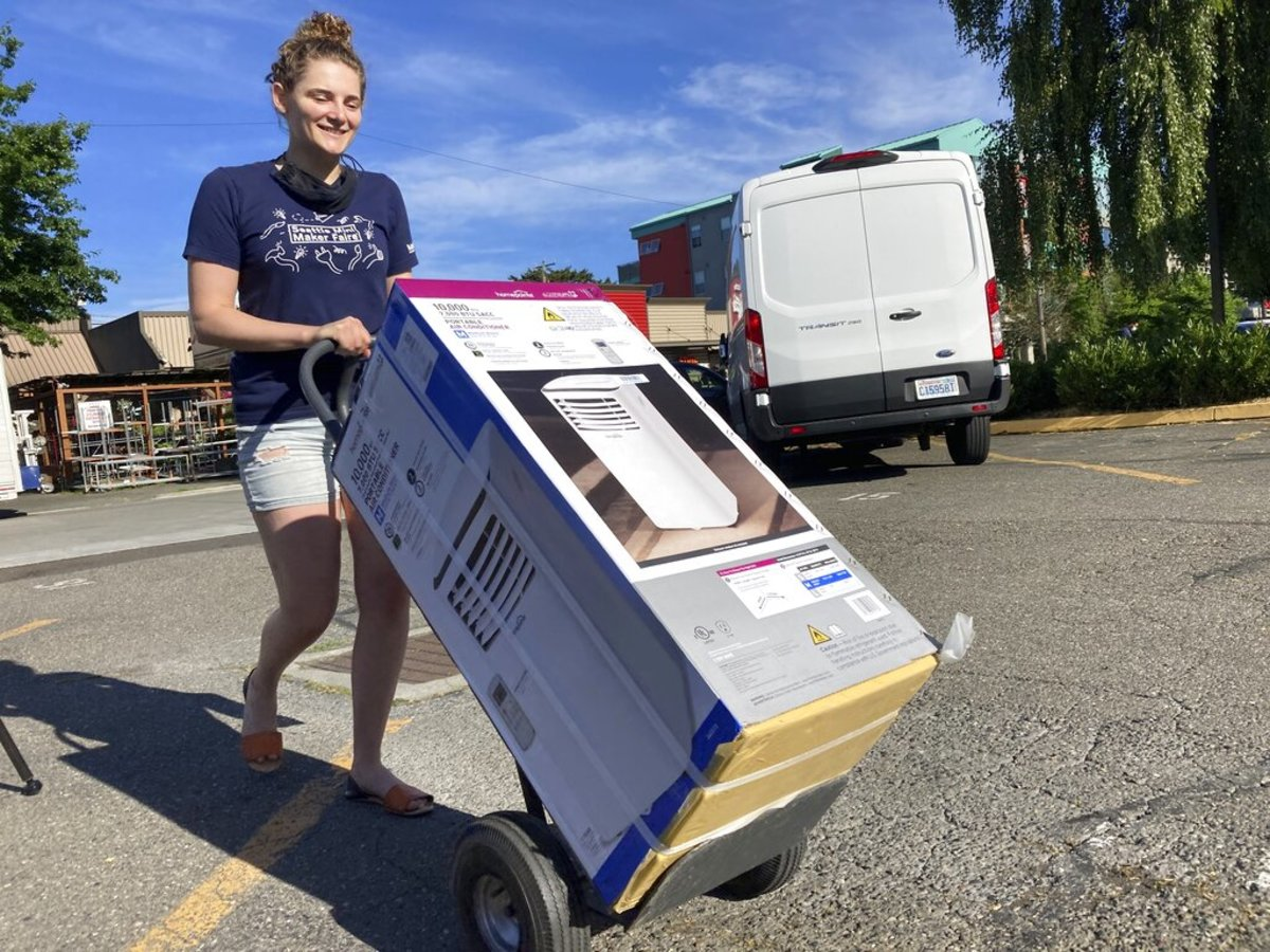 Sarah O'Sell transports her new air conditioning unit to her nearby apartment on a dolly in Seattle on Friday, June 25, 2021. O'Sell snagged one of the few AC units available at the Junction True Value Hardware as Pacific Northwest residents brace for an unprecedented heat wave that has temperatures forecasted in triple-digits. (AP Photo/Manuel Valdes)