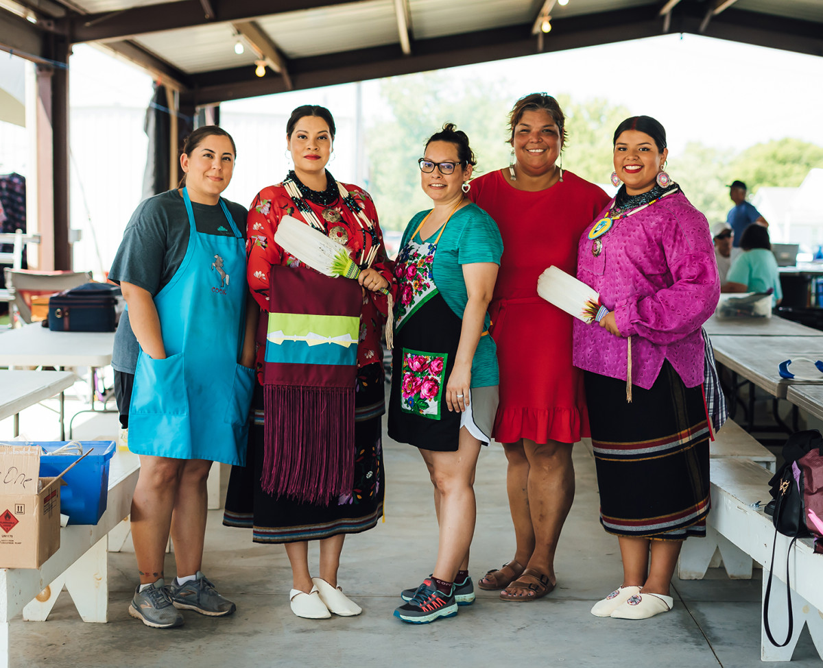 """From left, Grayhorse cook Alyssa Goodfox, Indigenous actress Cara Jade Myers, Tara Damron, Janese Sieke and Osage Nation Princess Gianna Sieke at the Grayhorse District camp on June 24, 2021. Sieke dressed Myers in Osage clothes to honor her for her work on the upcoming film, """"Killers of the Flower Moon."""" (Photo by Cody Hammer/Osage News)"""
