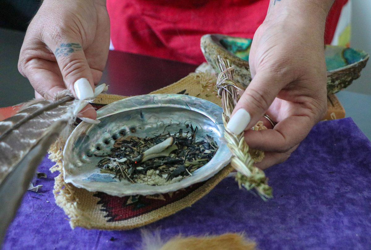 Andrea Klimas, the clinical director and a talking circle facilitator at Native American Connections, burns sage in a shell as part of a spiritual ceremony representing the four elements: earth, air, wind and fire. (Photo by Gianluca D'Elia/Cronkite News)