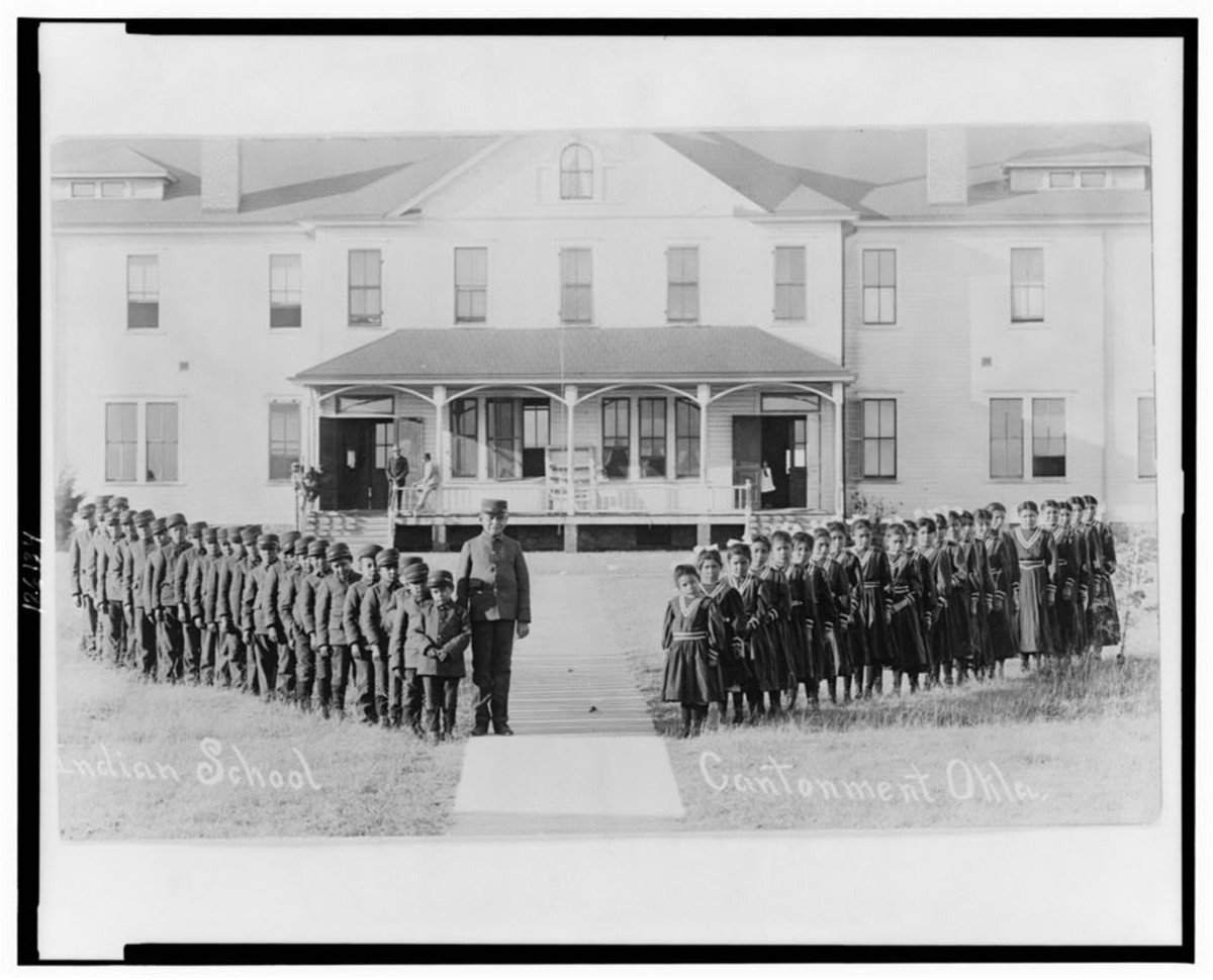 Uniformed boys and girls pose with their teacher in front of the Indian boarding school in Cantonment, Oklahoma, in 1909. (Photo courtesy of the Library of Congress)