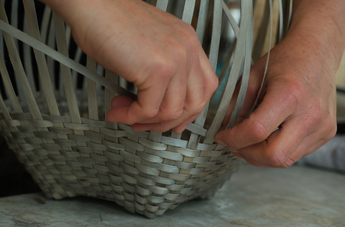 Artisan April Stone of the Bad River Band of Ojibwe makes a basket from black ash wood bark at her studio on the Bad River Reservation in Wisconsin in March 2021. She is now worried the trees are threatened by an invasive beetle. (Photo by Mary Annette Pember/Indian Country Today)