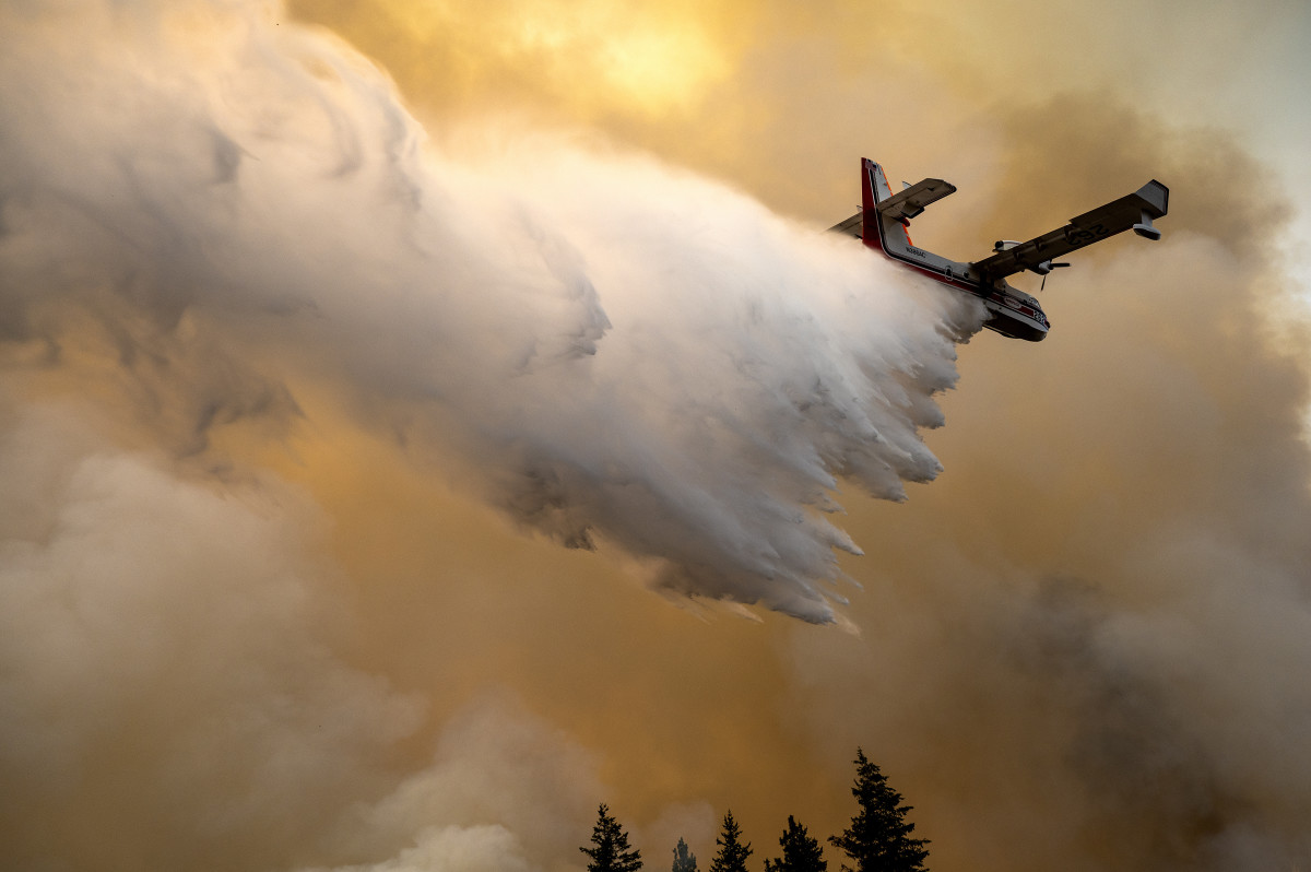 A scoop plane drops water onto a burning ridge in Washington state where a fire line had been created by crews of wildland firefighters, Monday, July 12, 2021 at the Lick Creek Fire, south of Asotin, Wash. (Pete Caster/Lewiston Tribune via AP)