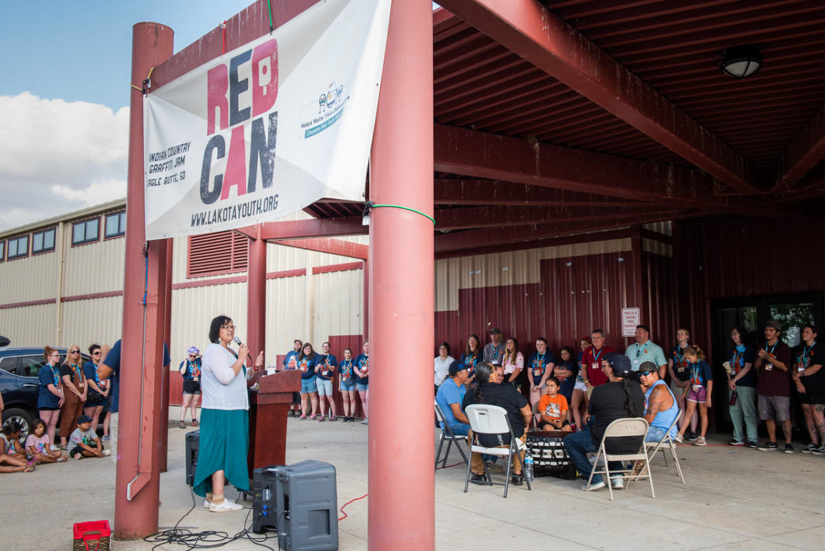 Pictured: Julie Garreau, Cheyenne River Youth Project's Executive Director, addresses the RedCan 2021 crowd at the evening drum circle with Wakinyan Maza.