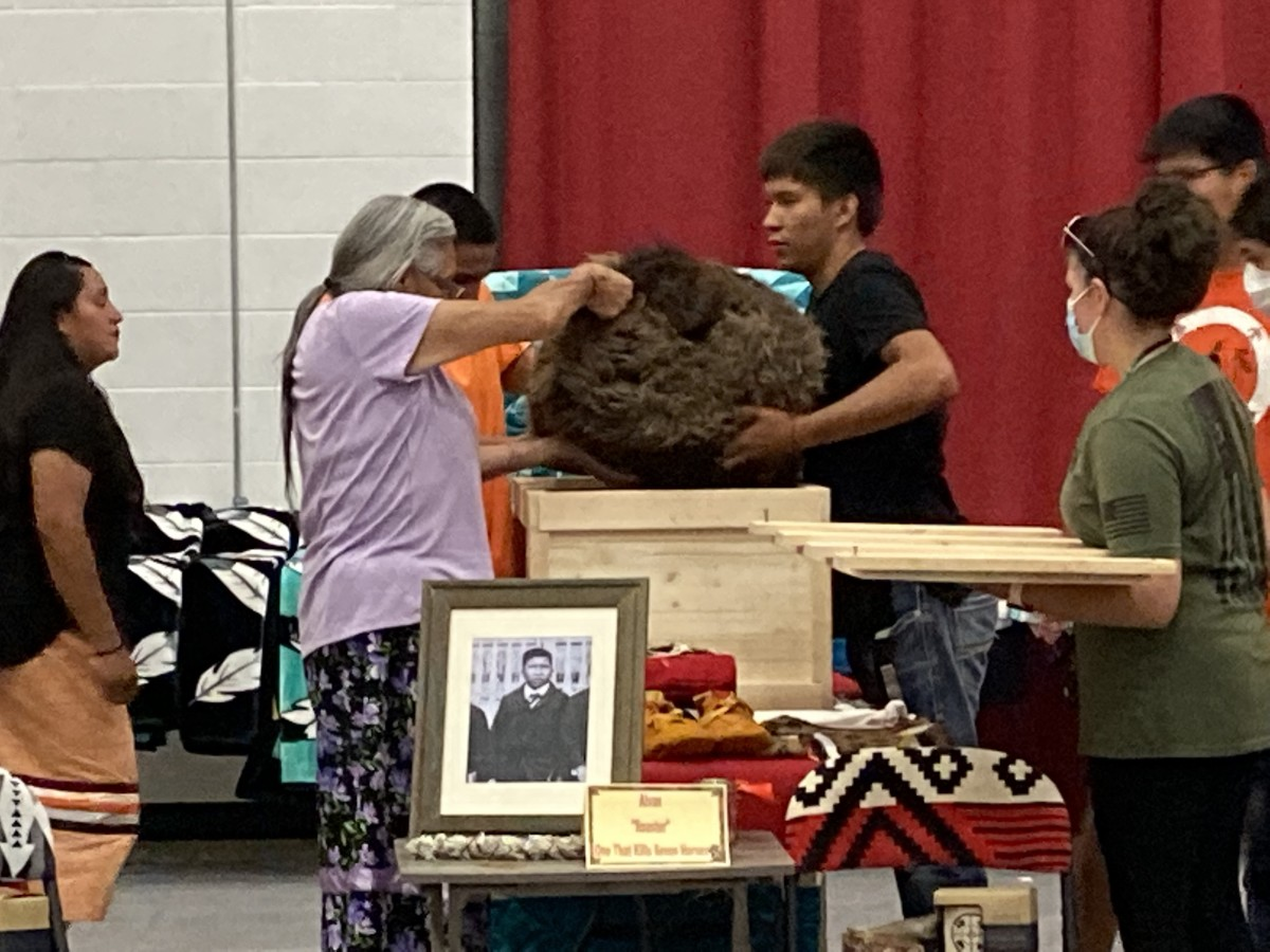 The disinterred remains of nine Rosebud Sioux children were wrapped in buffalo robes and placed in cedar boxes for their final trip home to South Dakota, more than 140 years after they were forced to attend the Carlisle Indian Industrial School in Pennsylvania. Here, Ione Quigley, left, Rosebud's tribal historic preservation officer, helps removes the remains from a box for a ceremony to honor their return on Friday, July 16, 2021. (Photo by Vi Waln for Indian Country Today)
