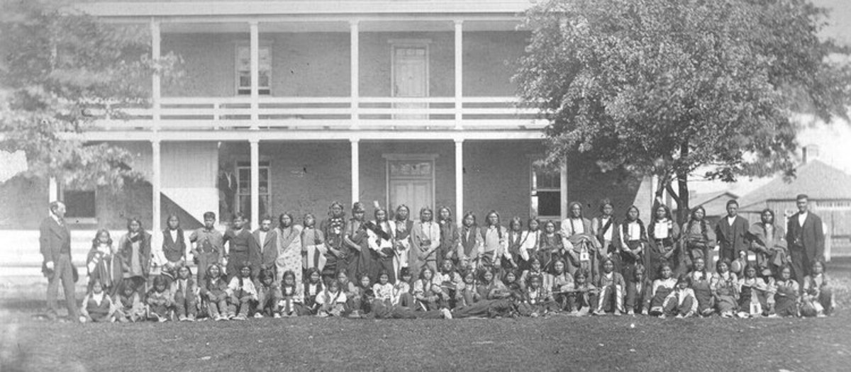 A group portrait shows the first male students to arrive at the Carlisle Indian Industrial School from Pine Ridge and Rosebud on October 6, 1879. Several of the boys in the photo later died and were buried at the school for more than 140 years before finally being sent to their relatives in South Dakota in July 2021. School founder Richard Henry Pratt is standing at left, and interpreter Charles Tackett is standing at right. (Photo courtesy of the Cumberland County Historical Society)