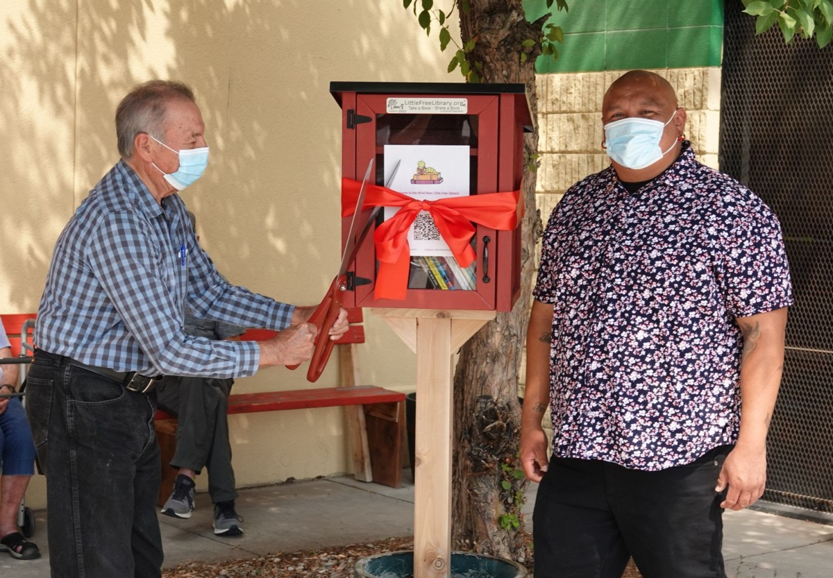 Pictured: John St. Clair cuts a ribbon to open the Wind River Little Free Library.