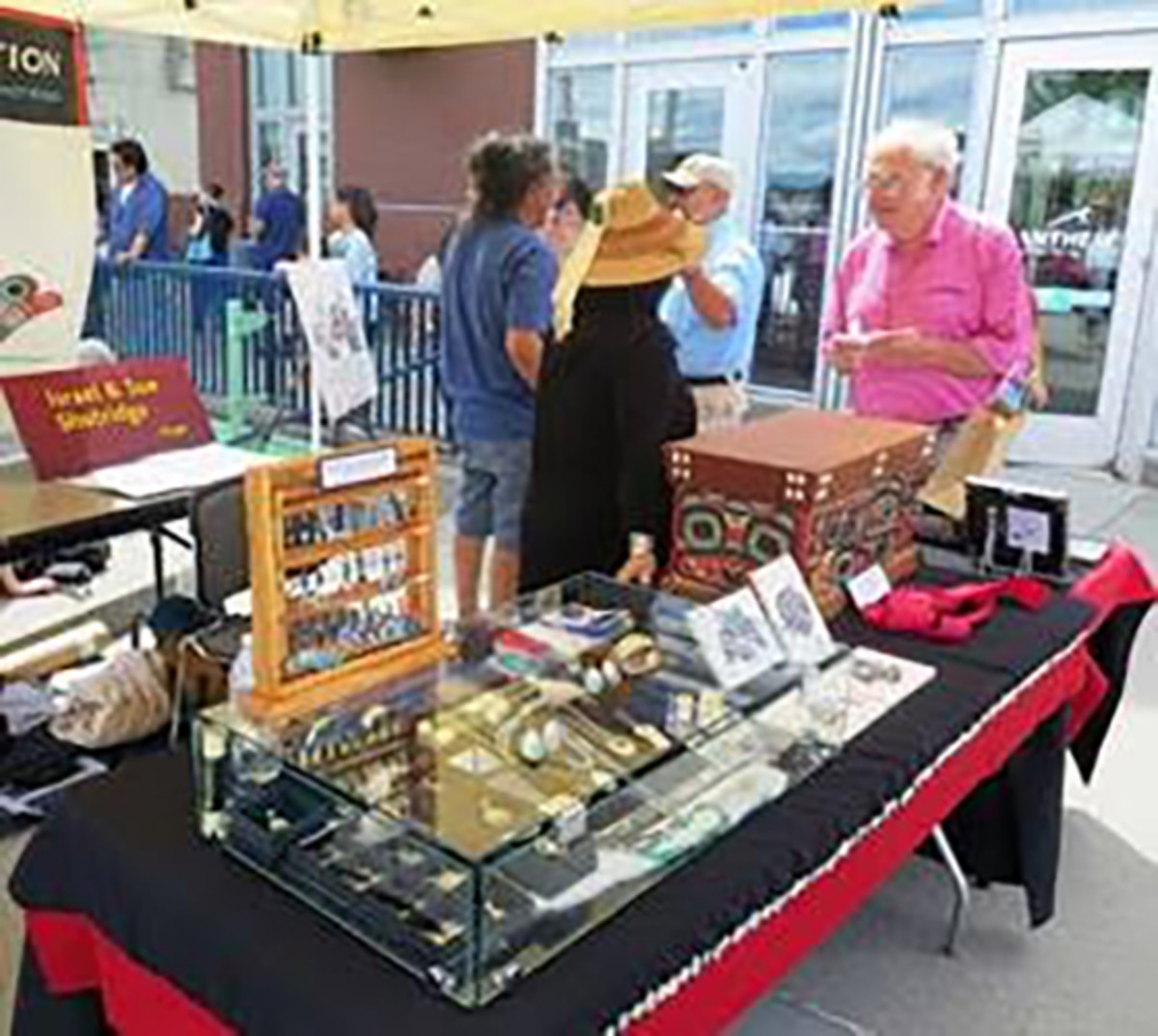 Pictured: IN THE SPIRIT Arts Market and Northwest Native Festival, vendor talking with visitors on the plaza at the Washington State History Museum (left) and visitors looking at Native carving. Visitors can shop among multiple artist vendors for a wide range of original art, textiles, leather goods, carvings, and more.