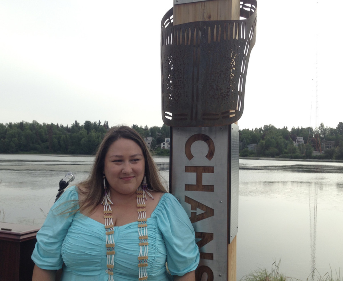 """PLACE NAMES Artist Melissa Shaginoff standing next to the place-name marker for """"Chanshntnu"""", or Grassy Creek, the Dena'ina name for Westchester Lagoon. The artwork represents a fire bag decorated with dentalium shells. (Photo by Joaqlin Estus)."""