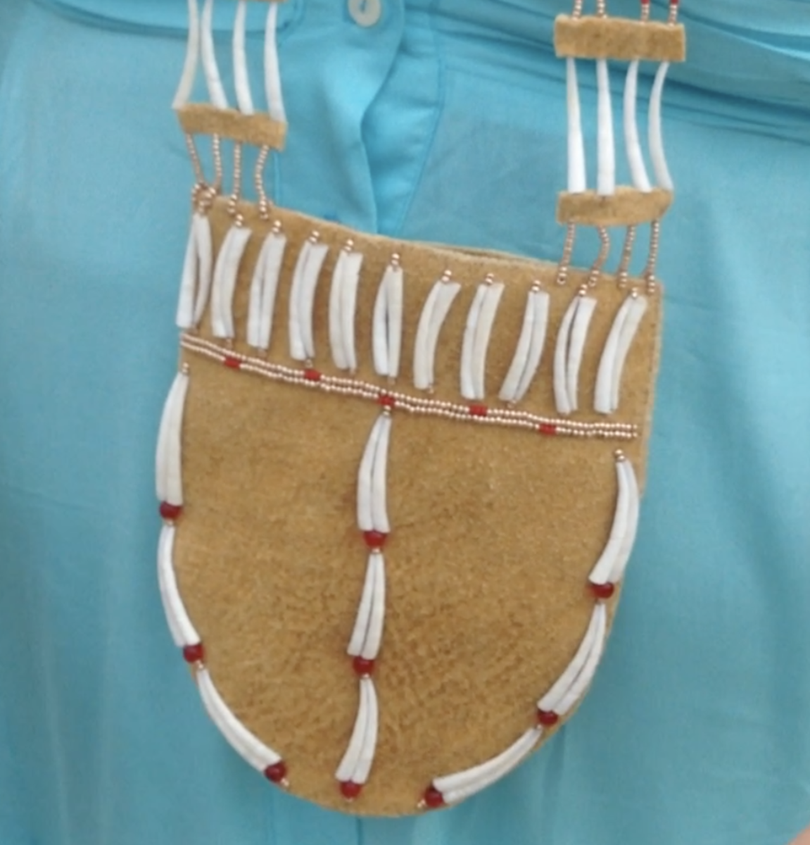 PLACE NAMES Shown here is a Dena'ina firebag necklace featuring dentalium shells. Historically the bag was used to carry tools and tinder for building fires. It's valued for its beauty and as a utilitarian object, according to the artist who made it, Melissa Shaginoff, Ahtna Athabascan and Paiute. She said it symbolizes the responsibility toward community, stewardship of the land, and leadership. Aug. 3, 2021, at Westchester Lagoon in Anchorage, Alaska. (Photo from video by Joaqlin Estus).