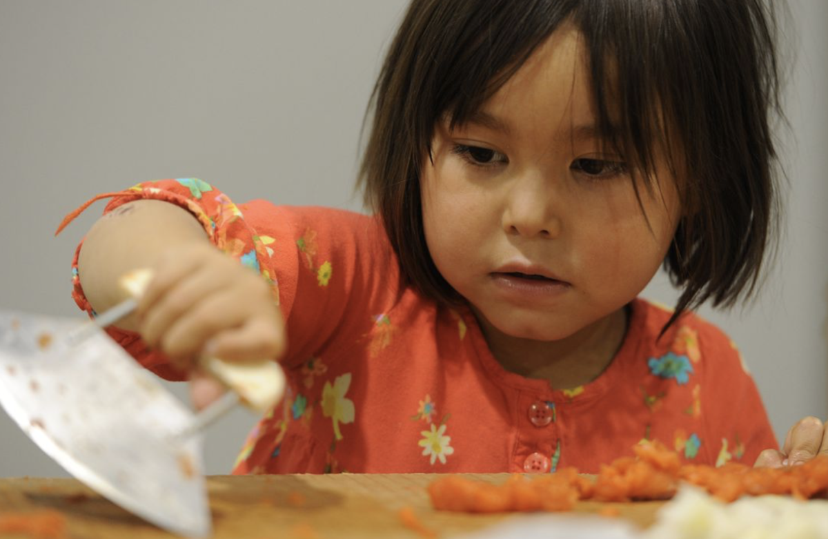 The future generations: a young Alaska Native girl cuts salmon with an ulu at the annual Elders and Youth Conference.