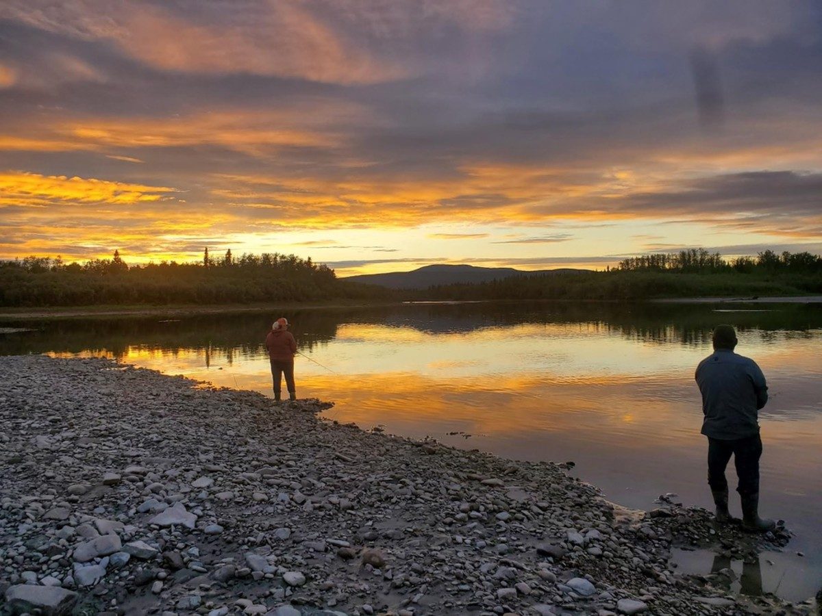 Where residents usually fish with nets to catch fish in quantities, a couple uses rods and reels to harvest non-salmon species at the mouth of the Melozi River, a tributary on the Yukon river. (Photo by Serena Fitka, Yukon River Drainage Fisheries Association).