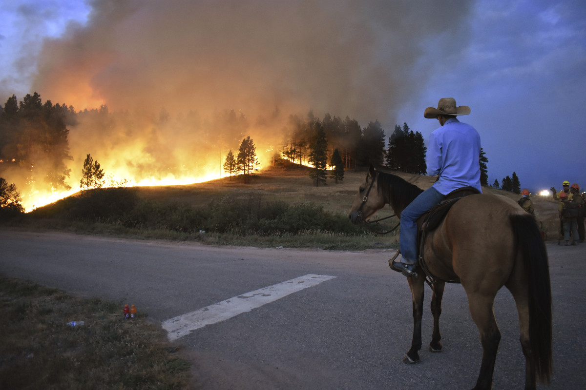Rowdy Alexander watches from atop his horse as a hillside burns on the Northern Cheyenne Indian Reservation, Wednesday, Aug 11, 2021, near Lame Deer, Mont. The Richard Spring fire was threatening hundreds of homes as it burned across the reservation. (AP Photo/Matthew Brown)