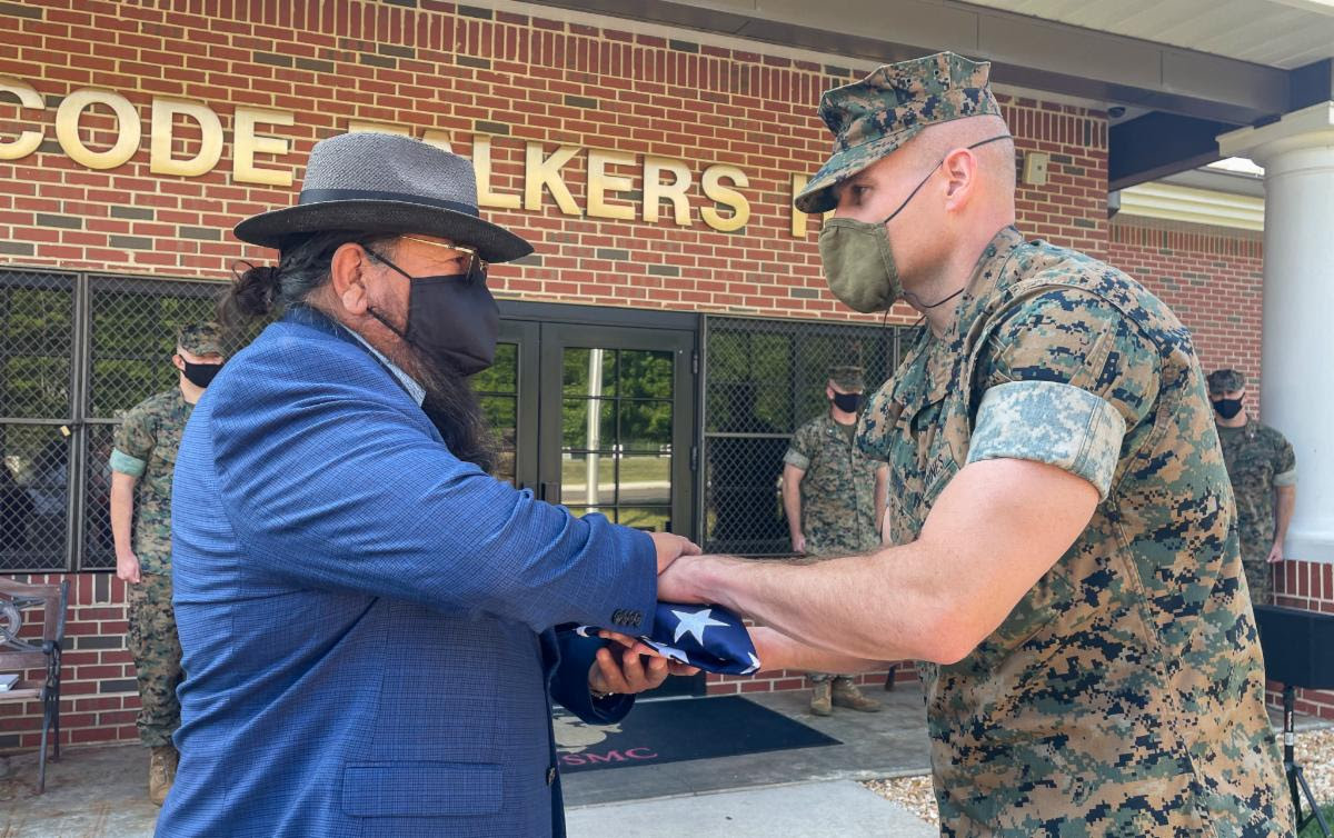 Pictured: Navajo Nation Delegate Raymond Smith, Jr. receives flag from Master Gunnery Sergeant, Dennis M. Romo at Code Talkers Hall in Quantico, Virginia.