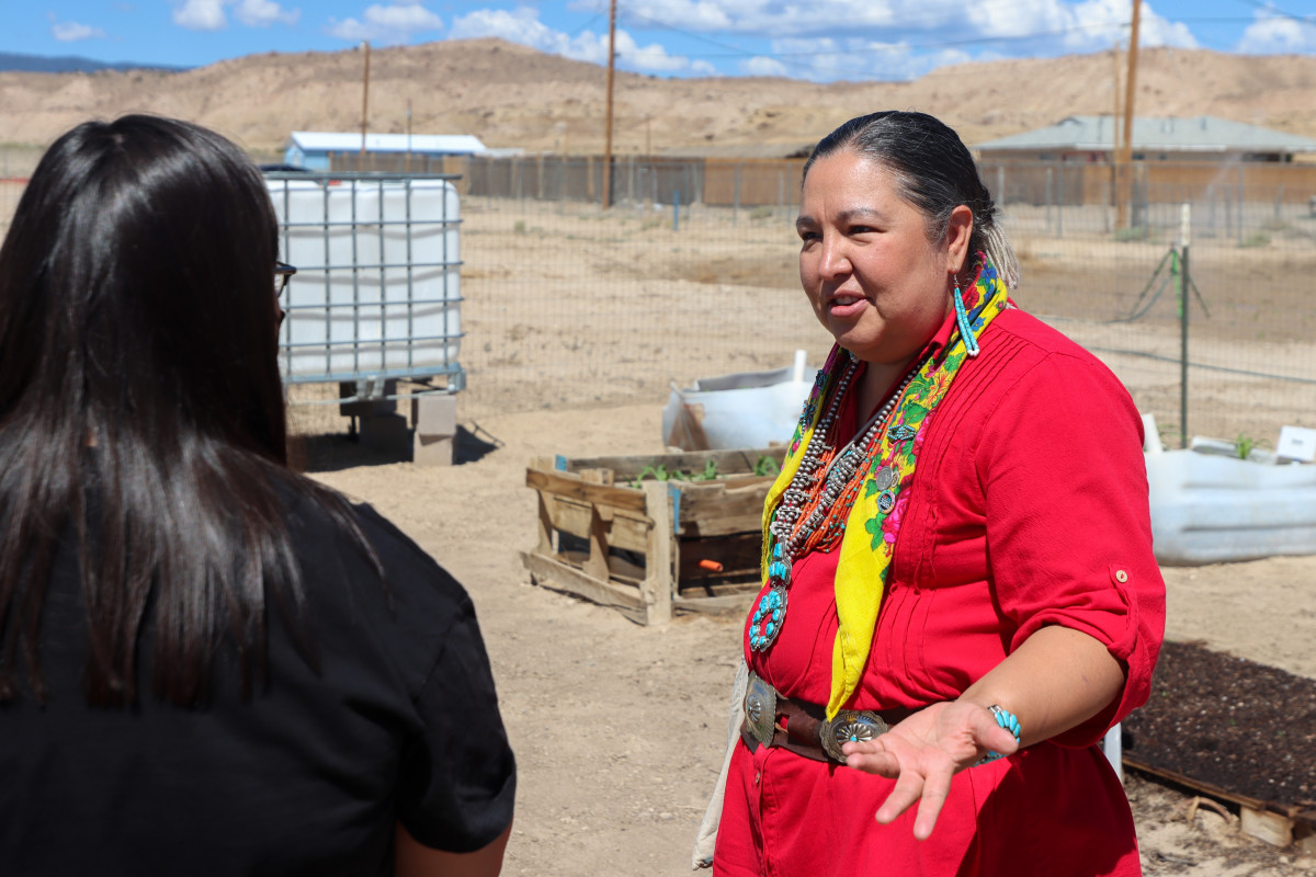 Amber Kanazbah Crotty, a delegate to the Navajo Nation Council, speaks with a youth volunteer in a community garden at the local chapter house in Sheep Springs, N.M., on July 7, 2021. Crotty is trying to expand family advocacy centers in the Navajo Nation to better serve survivors of sexual assault and child sexual abuse. (Brendon Derr / Howard Center for Investigative