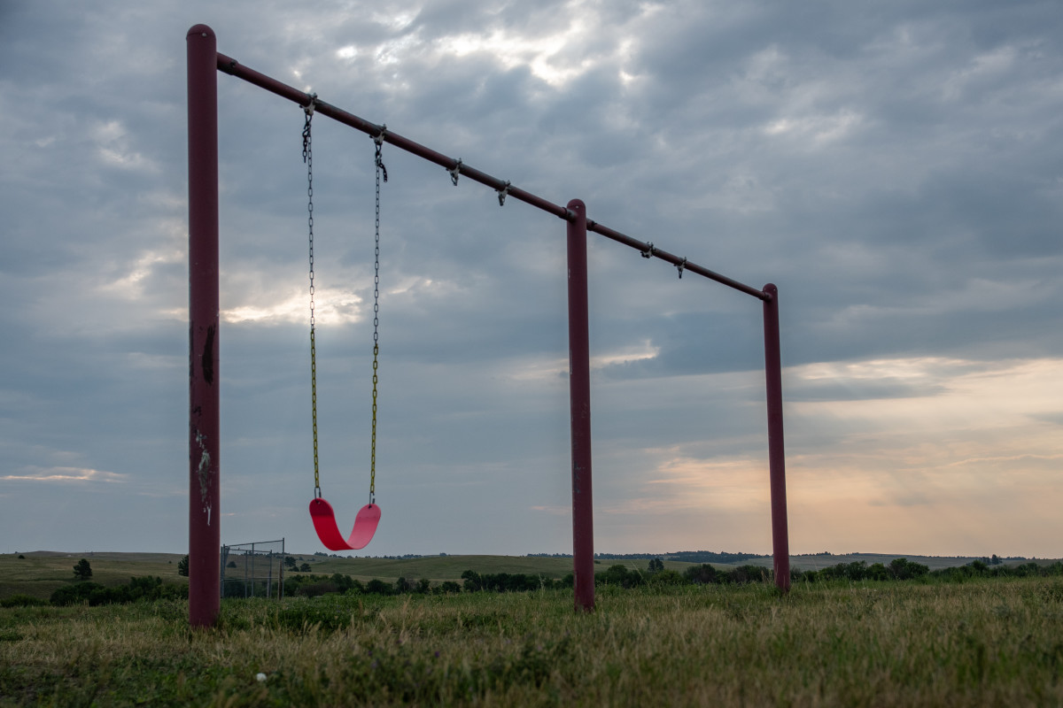Grass grows tall at an empty playground near the Wounded Knee Massacre Monument on the Pine Ridge Indian Reservation in South Dakota on July 21, 2021. In the void between the federal government's prosecution of major crimes in Indian Country and Native Americans' limited judicial authority, tribes are taking a variety of approaches to healing and justice. (Isaac Stone Simonelli / Howard Center for Investigative Journalism)
