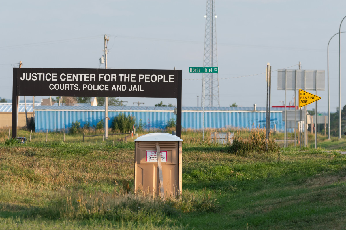 A sign for the Justice Center For The People, a tribal public safety center, is pictured on July 22, 2021, near a southern entrance to the Pine Ridge Indian Reservation in South Dakota. Experts say tribes need more consistent federal funding for their justice systems. (Isaac Stone Simonelli / Howard Center for Investigative Journalism)