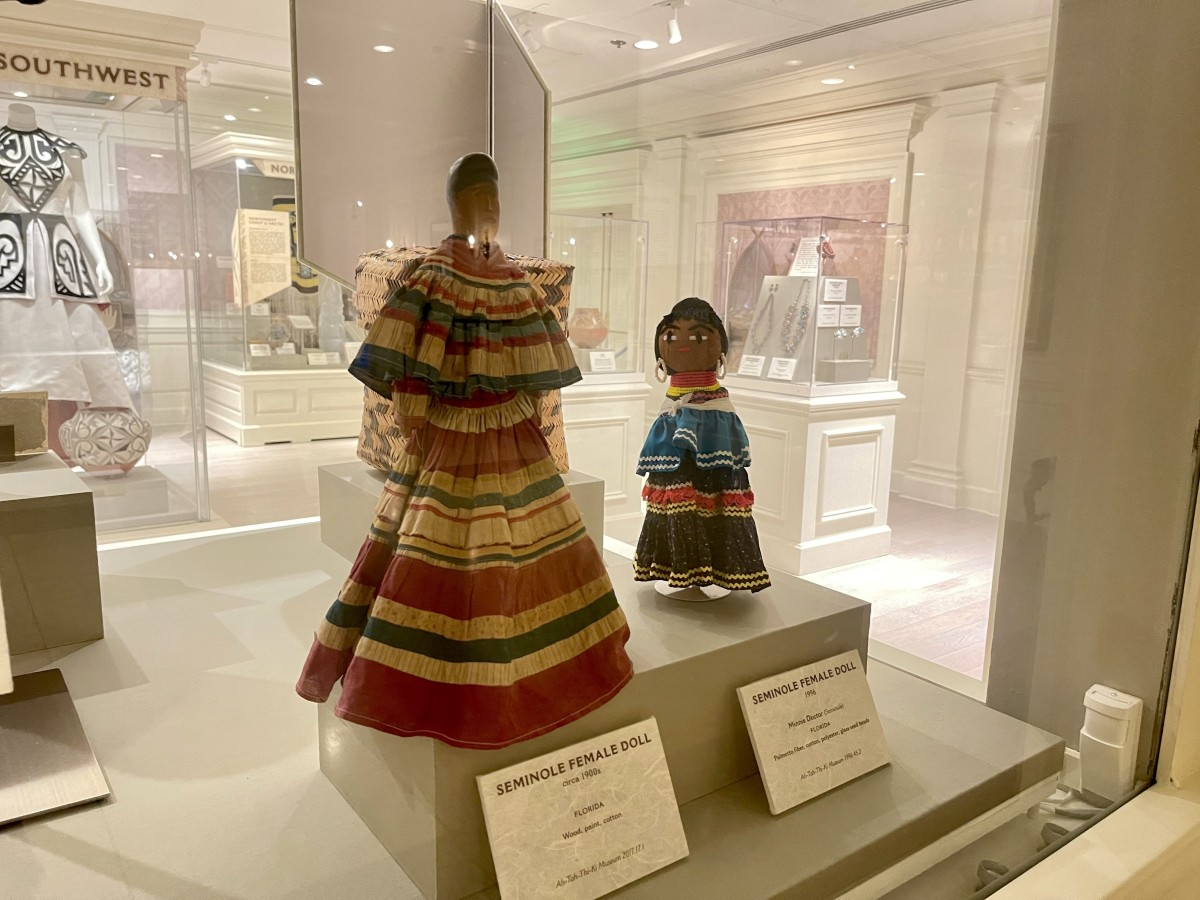 A Seminole doll from the 1900s, left, is made of wood and features a baby on the woman's back. A new version, made from palmetto fibers by Seminole artisan Minnie Doctor in 1996, wears similar clothing. The dolls are part of an exhibit of items on loan from the Seminole Tribe of Florida's Ah-Tah-Thi-Ki Museum to the American Heritage Gallery at Disney's Epcot Center in Orlando, Florida. The Ah-Tah-Thi-Ki Museum closed to visitors during the COVID-19 pandemic but is set to reopen Aug. 21, 2021. (Photo courtesy of Walt Disney World Resort)