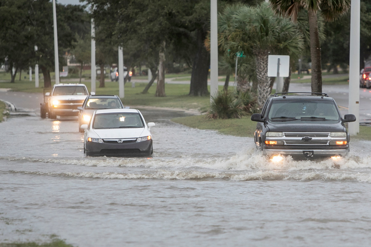 Vehicles drive through Hurricane Ida storm surge floodwater at U.S. 90 and Miramar Avenue in Biloxi, Miss., Sunday, Aug. 29, 2021. The Honda Civic, stalled out in the middle of the street as it tried to drive through the water. (Justin Mitchell/The Sun Herald via AP)