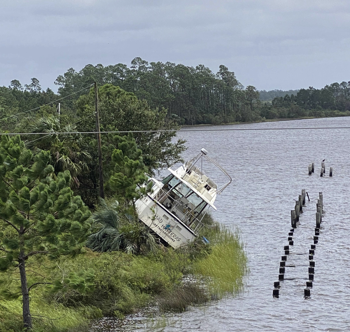 Boat washed up on the shoreline of Bayou Portage in Pass Christian, Miss. from the effects of Hurricane Ida on Monday, Aug. 30, 2021. (Hunter Dawkins/The Gazebo Gazette via AP)/The Gazebo Gazette via AP)