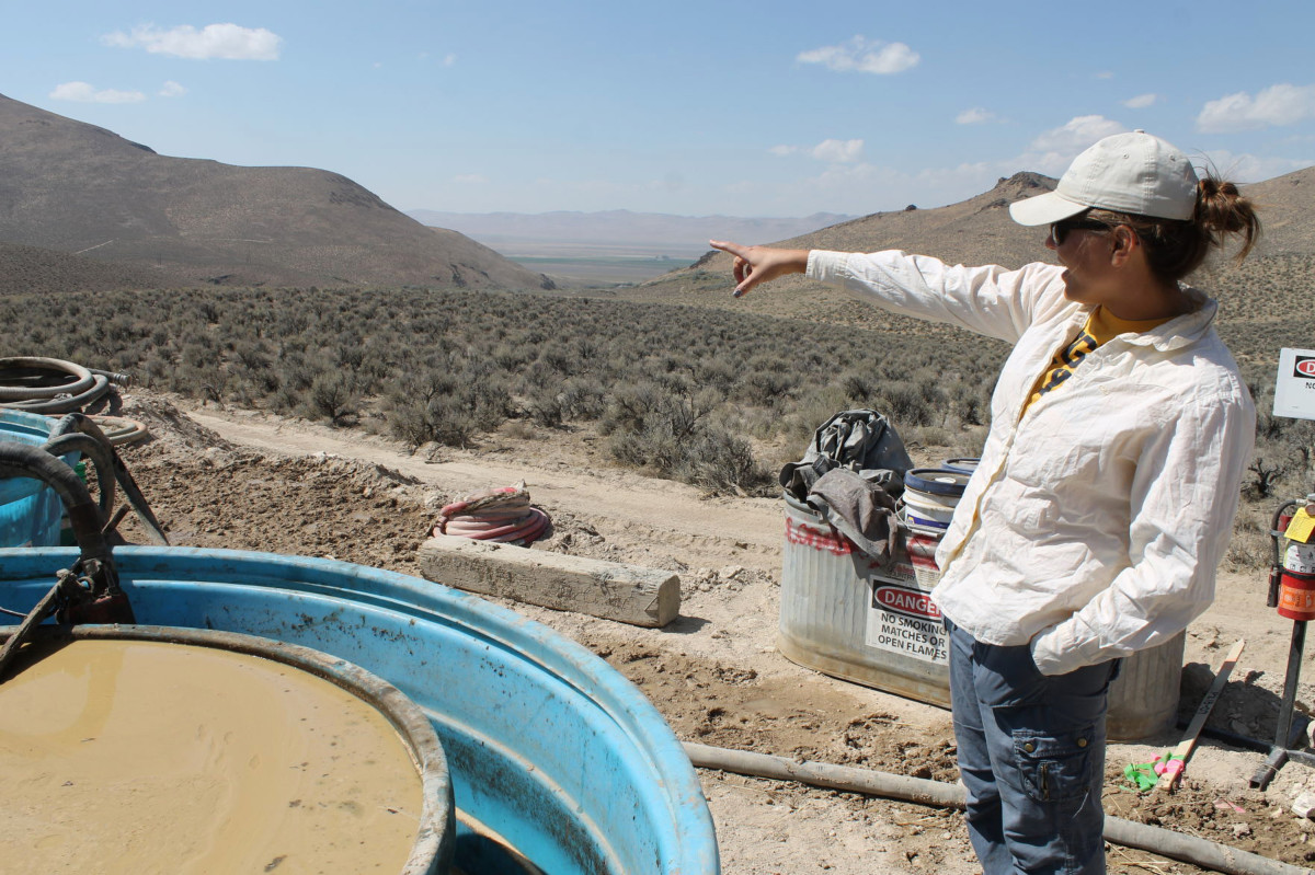 In this Sept. 13, 2018, file photo, Melissa Boerst, a Lithium Nevada Corp. geologist, points to an area of future exploration from a drill site at the Thacker Pass Project in Humboldt County, Nev. A federal judge has denied tribal leaders' bid to temporarily block digging for an archaeological study required before construction can begin for a Nevada lithium mine on what they say is sacred land where their ancestors were massacred more than century ago. U.S. District Judge Miranda Du refused three tribes' request for a preliminary injunction blocking the trenching planned to collect samples near the Oregon line at the site of the largest known lithium deposit in the United States. (Suzanne Featherston/The Daily Free Press via AP, File)
