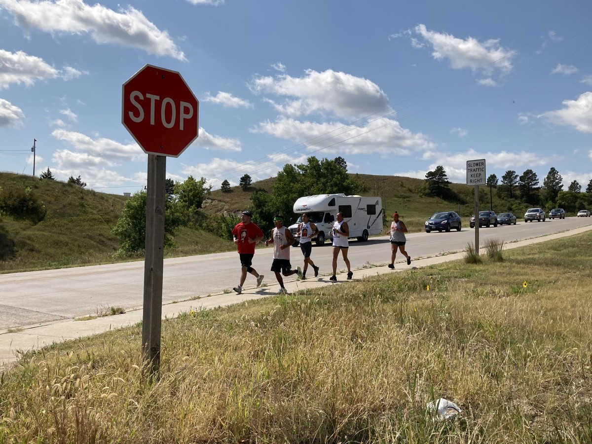 Members of the Sicangu Oyate ki Iyanka group run down the west hill into the Rosebud Indian Reservation in South Dakota to finish the first day of a relay drawing attention to Missing and Murdered Indigenous Women. The white RV shown on the roadway is crossing through tribal lands on its way from Washington state to Washington, D.C. to draw attention to MMIW. (Photo by Vi Waln for Indian Country Today)