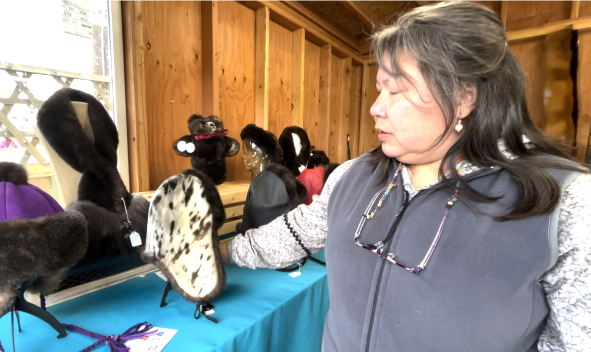 Amy Rogde, Dena'ina Athabascan, shows one of her sealskin hats lined with sea otter fur, one of her best-sellers. Sept. 5, 2021 at the Alaska State Fair (Photo by Joaqlin Estus, Indian Country Today).